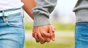 Midsection of a couple holding hands
